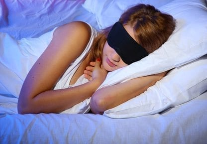 young beautiful woman with eye mask sleeping on bed in bedroom