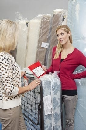 Young woman holding price list while looking at mother in furniture store